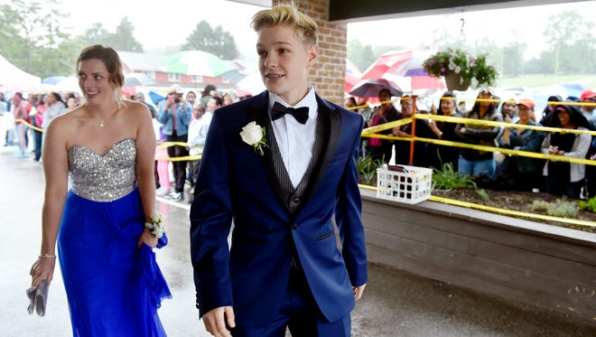 Bishop McDevitt High School student Aniya Wolf, right, and her date arrive for William Penn's prom at Wisehaven Catering & Events in Windsor Township on Saturday. Wolf, who identifies as lesbian, said she was barred from attending her school's prom earlier in the month, due to the Catholic school's dress code policy requiring girls to wear dresses. William Penn's principal invited Wolf to attend the school's prom, where she and her date were greeted with cheers by parents and friends who gathered to watch students arrive.