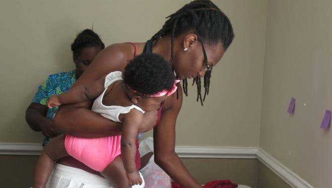 A young mom and her baby look at some clothes during the Healthy Start's Giving Closet.