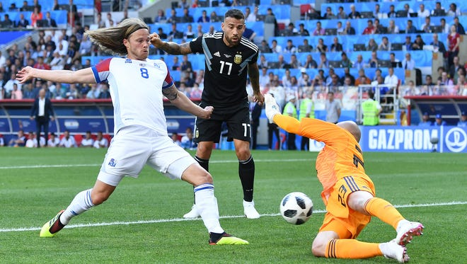 Jun 16, 2018; Moscow, Russia; Iceland midfielder Birkir Bjarnason (8) tries to get to the ball as Argentina defender Nicolas Otamendi (17) and goalkeeper Wilfredo Caballero (23) defend in Group D play during the FIFA World Cup 2018 at Spartak Stadium. Mandatory Credit: Tim Groothuis/Witters Sport via USA TODAY Sports