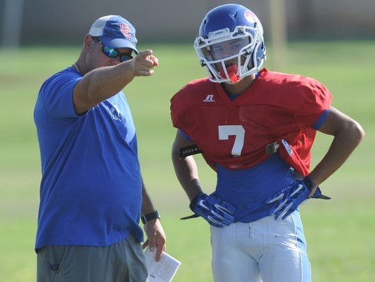 Cooper coach Todd Moebes, left, talks to sophomore safety LaDainian Diaz after a play during practice Sept. 4 at the Cougars' practice field. Diaz, playing his first varsity game,, picked off two passes in the Coogs' 48-35 victory over Keller in the season opener.
