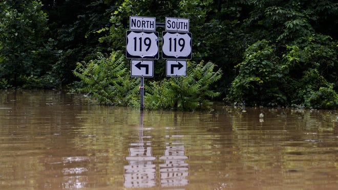 FILE - In this June 24, 2016 file photo, road signs signaling to US 119 along Frame Road in Elkview, W.Va., are surrounded by flood waters. A year after the floods, the owner of the Crossings Mall in Elkview is replacing a washed-out bridge that made the mall inaccessible and forced hundreds to be laid off or displaced, although two anchor stores are returning. A Kroger plans to reopen in August 2017, and Kmart has said it will reopen once the bridge is rebuilt. (Sam Owens/Charleston Gazette-Mail via AP)