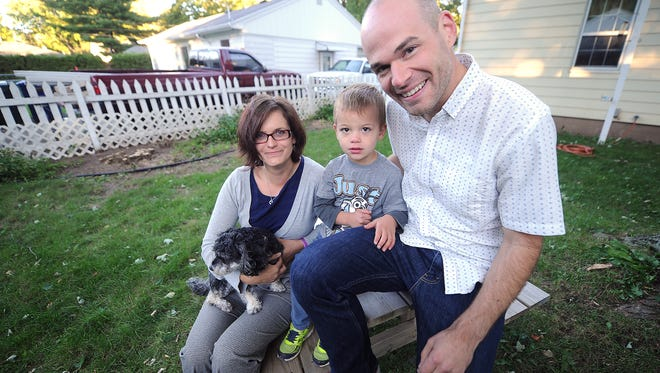 Efrem Kerbel, center, with his mom Sarah, left, and dad Andrew in the yard of their De Pere home.