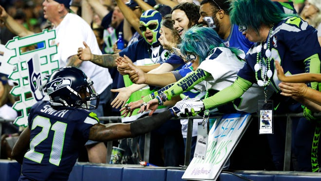 Seattle Seahawks cornerback Tye Smith (21) greets fans in the end zone during the second half of a preseason NFL football game against the Dallas Cowboys, Thursday, Aug. 25, 2016, in Seattle.