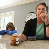 Mollie Garden holds a bottle of medical cannabis currently taken by her daughter Madeline to treat her seizure disorder. The Gardens have established residency in Colorado and traveled there to obtain the drug in the past.
