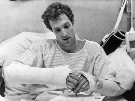 Andy Coan tries to use a pen despite two broken wrists suffered in an automobile accident 1979.