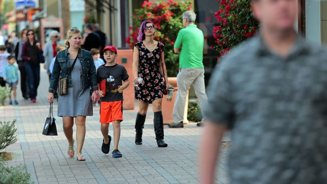 With four days left until Christmas, shoppers walk along El Paseo past retail storefronts on Sunday, December 21, 2014 in Palm Desert, Calif.