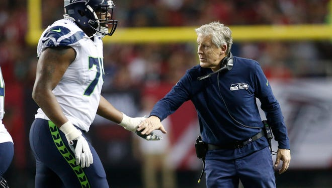 Seahawks coach Pete Carroll shakes rookie offensive tackle George Fant's hand during the second quarter of Saturday's 36-20 NFC divisional playoff loss at Atlanta.
