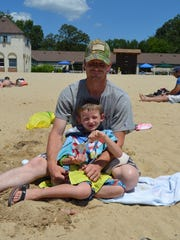 Marcus Smith and Riley Smith, 6, both of Woodstown relax on the beach at Parvin State Park during the Christmas in July event.
