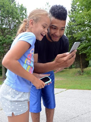 "Myiah Brown, 9, smiles as she and her dad, Jordan, catch a Pokemon with the new ""Pokemon Go"" app on his phone Monday, July 11, behind Michigamme Elementary."