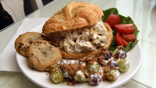 A chicken salad croissant sandwich, made with sweetcorn, red onions, celery and fresh chicken on a buttery croissant, is a popular menu item at The Crumb and Cup Cafe in New Concord. The sandwich is served with a side and two freshly baked cookies or a brownie. The crunchy pecan grape salad shown is a seasonal side option.
