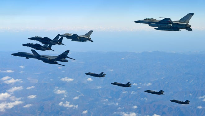 This handout taken and released by the South Korean Defence Ministry in Seoul on Dec. 6, 2017 shows a US Air Force B-1B Lancer bomber, two US F-35A and two US F-35B stealth jets flying over South Korea with South Korea's two F-16 and two F-15K fighter jets during a joint military drill.