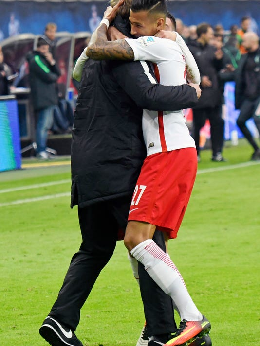 Leipzig coach Ralph Hasenhuettl, left, celebrates together with Leipzig's Davie Selke, right, after scoring a goal during the German first division Bundesliga soccer match between RB Leipzig and SV Werder Bremen in Leipzig, Germany, Sunday, Oct. 23, 2016. (AP Photo/Jens Meyer)