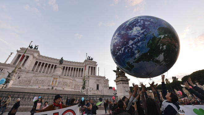 People play with a giant balloon representing Earth at Piazza Venezia in Rome during a rally calling for action on climate change before a meeting of world leaders.