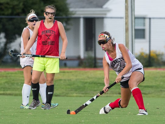 A Bennett field hockey player passes the ball during