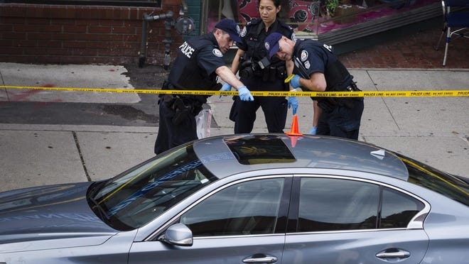Police investigate a car at the scene of a shooting in Toronto, on Monday, July 23, 2018. Police were trying Monday to determine what prompted a man to go on a shooting rampage in a popular Toronto neighborhood on Sunday.