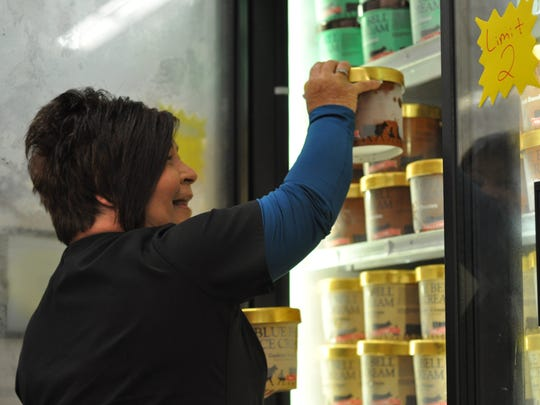 Patti Bernard picks up two half-gallons of Blue Bell ice cream for her husband early Monday morning just after the products were restocked at Kroger in Alexandria.