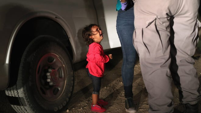 A two-year-old Honduran asylum seeker cries as her mother is searched and detained near the U.S.-Mexico border on June 12, 2018.