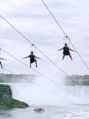 Tourists suspended above the water from zip lines make