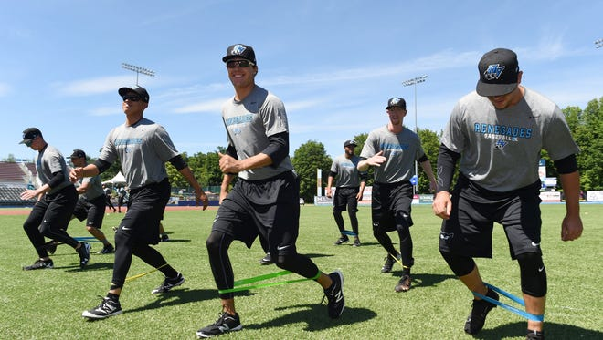 The Hudson Valley Renegades use elastic bands to stretch during pracitce on Wednesday at Dutchess Stadium in Fishkill.