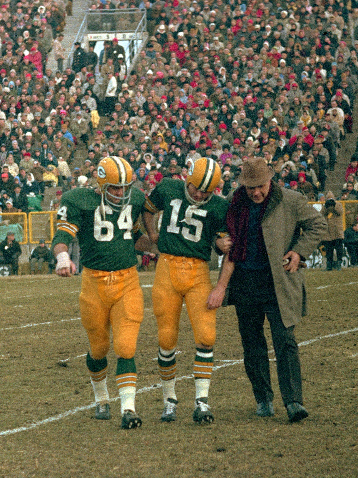 Green Bay Packers quarterback Bart Starr (15) is helped off the field by guard Jerry Kramer (64) and Dr. James Nellen after injuring his ribs on Green Bay's first play from scrimmage in a 13-10 victory over the Baltimore Colts in overtime in the Western Division championship game at Lambeau Field on Dec. 26, 1965. Starr had completed a pass to end Bill Anderson, who fumbled. Colts linebacker Don Shinnick recovered and returned it 25 yards for a touchdown. Starr was hurt while trying to stop one of Shinnick's blockers.