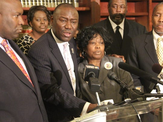 Benjamin Crump, hugging Barbara Dawson's cousin Martha Dickson, speaks to reporters Wednesday. He is flanked to the left by law partner Daryl Parks and the left by state Rep. Darryl Rouson, who are also representing the family.