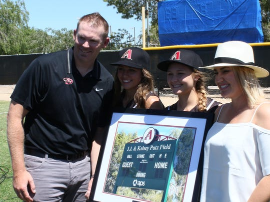Valley Lutheran softball players present the Putz family with a gift.