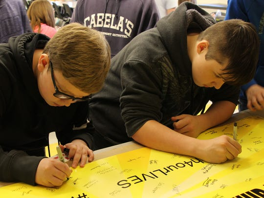 Windsor Middle School students sign a banner during their lunch period Monday for students at Marjory Stoneman Douglas High School in Florida.