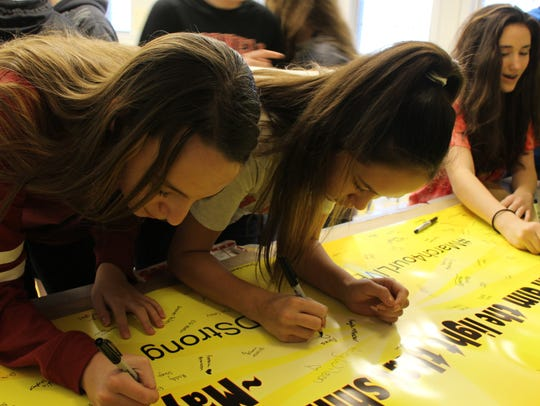 Windsor Middle School students sign a banner during