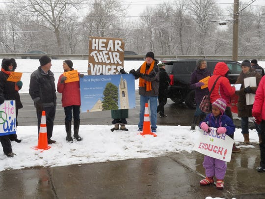 Community members support the walkout outside of Ithaca High School in Ithaca, N.Y. on National School Walkout Day on March 14, 2008. Pictured: (far left) Nancy Potter, of Newfield, (far right) Tziona Szajman and her 4-year-old daughter Eliyana, who is holding a sign.