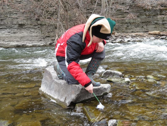 Nick Schill, 11, collects a sample as he participates