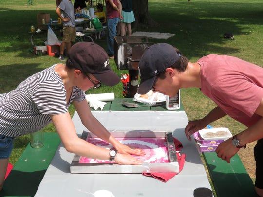 Vera Khovanskaya and Ethan Ritz work on a T-shirt.