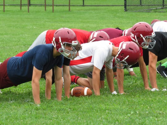 Ithaca High School football players do pushups during their first practice of the 2018 season.