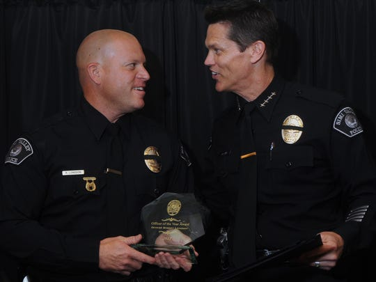 Simi Valley Police Officer Robert Longdon, left, is presented the Officer of the Year Award from former Chief of Police Mitch McCann during an awards luncheon at the Grand Vista Hotel in 2013.