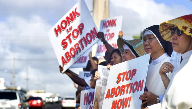 In this January 2009 file photo, parishioners, students, supporters and other participants wave their placards during the Annual Chain for Life event at the ITC intersection in Tamuning. Lawmakers are considering a bill that would impose stiff penalties against abortion doctors who fail to submit required information about abortions to the government.