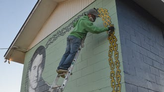Mural artist Bryan Deese adds dimension on the chain bordering his newest creation honoring professional skateboarder and Gallatin native Ray Underhill on a wall next to Gallatin's skate park.