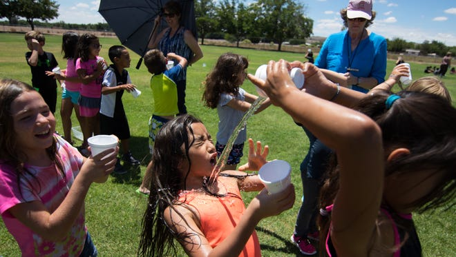 Second-grader Liana Galvan braces is doused in water by a classmate during Fairacres Elementary's Water Day held Wednesday, Aug. 3, 2016, to celebrate the end of the school's K-3 summer program.
