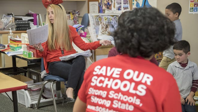 Tres Rios Service Academy Kindergarten teacher Thalia Page (left) and Special Education teacher's assistant Elizabeth Ramos both wear the red t-shirt to protest low pay and the state's failure to make significant efforts to address the issue.