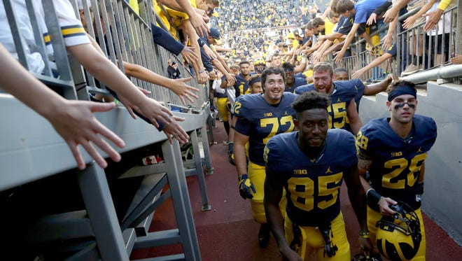 Fan reach out to get high fives from Michigan Wolverines players as they make their way up the tunnel after their 49-10 win over Penn State at Michigan Stadium in Ann Arbor on Saturday, Sept. 24, 2016.