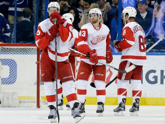 Detroit Red Wings players, from left, defenseman Danny DeKeyser, center Darren Helm (43) and left wing Justin Abdelkader react to the team's 1-0 loss to the Tampa Bay Lightning during Game 5 in a first-round NHL hockey Stanley Cup playoff series Thursday, April 21, 2016, in Tampa, Fla. (AP Photo/Chris O'Meara)