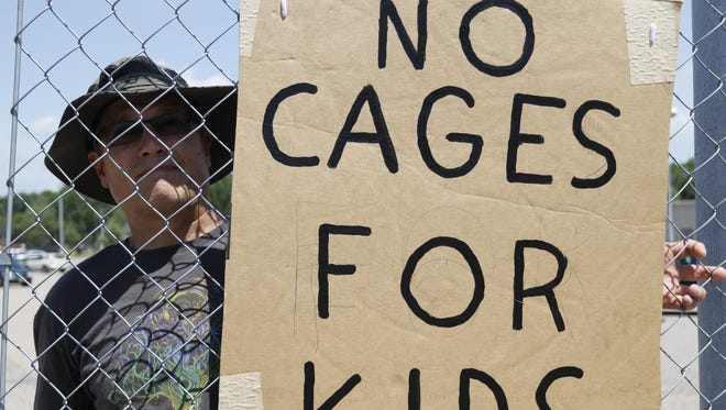 """Don Green of Plover carried a piece of chain link fence with a sign reading """"no cages for kids"""" during the Families Belong Together protest organized by NextGen Wisconsin along Division Street between Maria Drive and Fourth Avenue in Stevens Point, Wis. Saturday, June 30, 2018."""