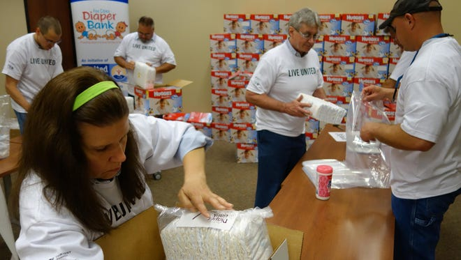 Kimberly-Clark employees help repack diapers for the Fox Cities Diaper Bank in 2015. More than 1,700 cases of diapers donated for the program were recently stolen from a warehouse.