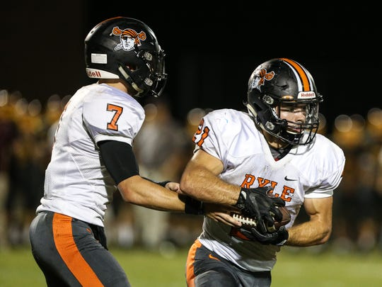 Ryle's Jacob Chisholm takes a handoff from quarterback Easton Pilyer during their game at Cooper, Friday, October 6, 2017.