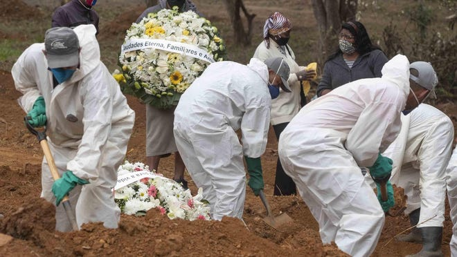 Relatives watch cemetery workers shovel dirt over the coffin of 47-year-old Paulo Roberto da Silva, who died of COVID-19, at the Sao Luiz cemetery in Sao Paulo, Brazil, Thursday, June 4, 2020.