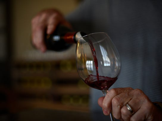 Craig Fletcher, owner, pours a glass of wine at Mona