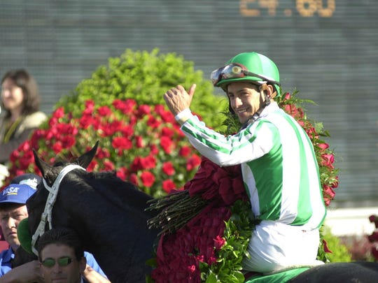 Wrapped in roses, Espinoza gave the thumbs up in the winner's circle.