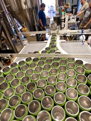 Iron Heart's mobile cannery in operation at the Fiddlehead Brewing Company in Shelburne on Thursday. The operation cleans, removes oxygen from, fills and seals the cans.