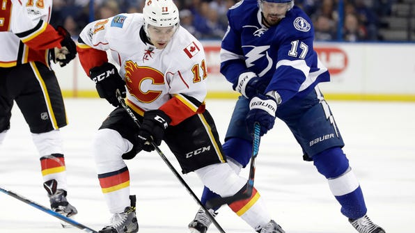 Calgary Flames center Mikael Backlund (11), of Sweden, gets hooked by Tampa Bay Lightning left wing Alex Killorn (17) during the first period of an NHL hockey game Thursday, Feb. 23, 2017, in Tampa, Fla. (AP Photo/Chris O'Meara)