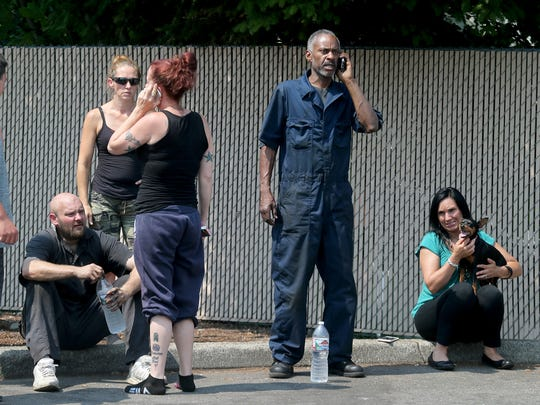 Workers from the automobile repair shop at 11th street and Callow in Bremerton on Thursday, watch the fire.