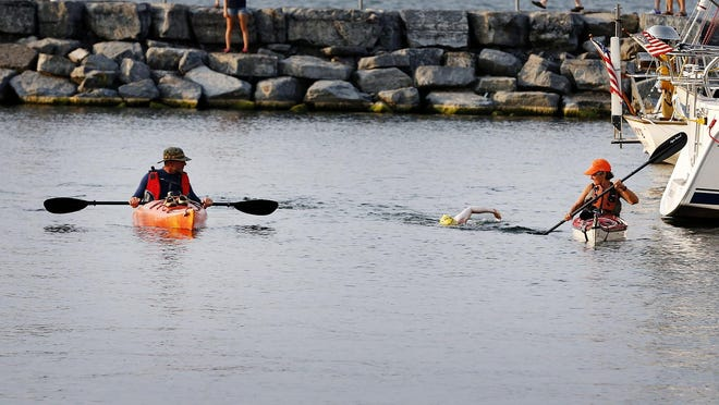 Bridgette Hobart Janeczko enters the last leg of swimming Seneca Lake in the Watkins Glen marina Saturday, Aug. 29, after swimming the near 38-mile lake nonstop. Her husband, Bob, left, and Louise Adie, right, of Trumansburg, escort Laneczko to the boat launch.