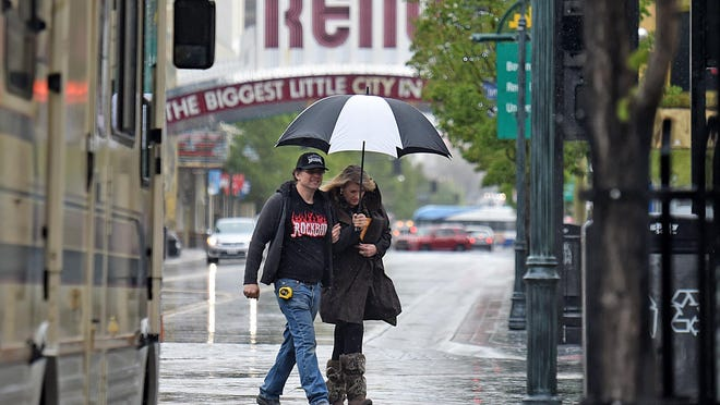 A file photo showing a couple crossing Second Street in downtown Reno during a rainy day.